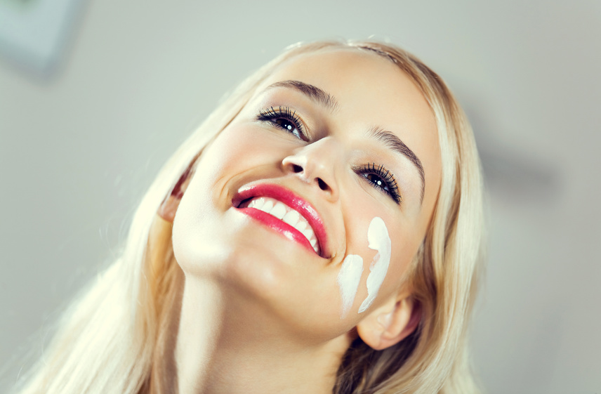 Portrait of young smiling lovely woman applying creme at home