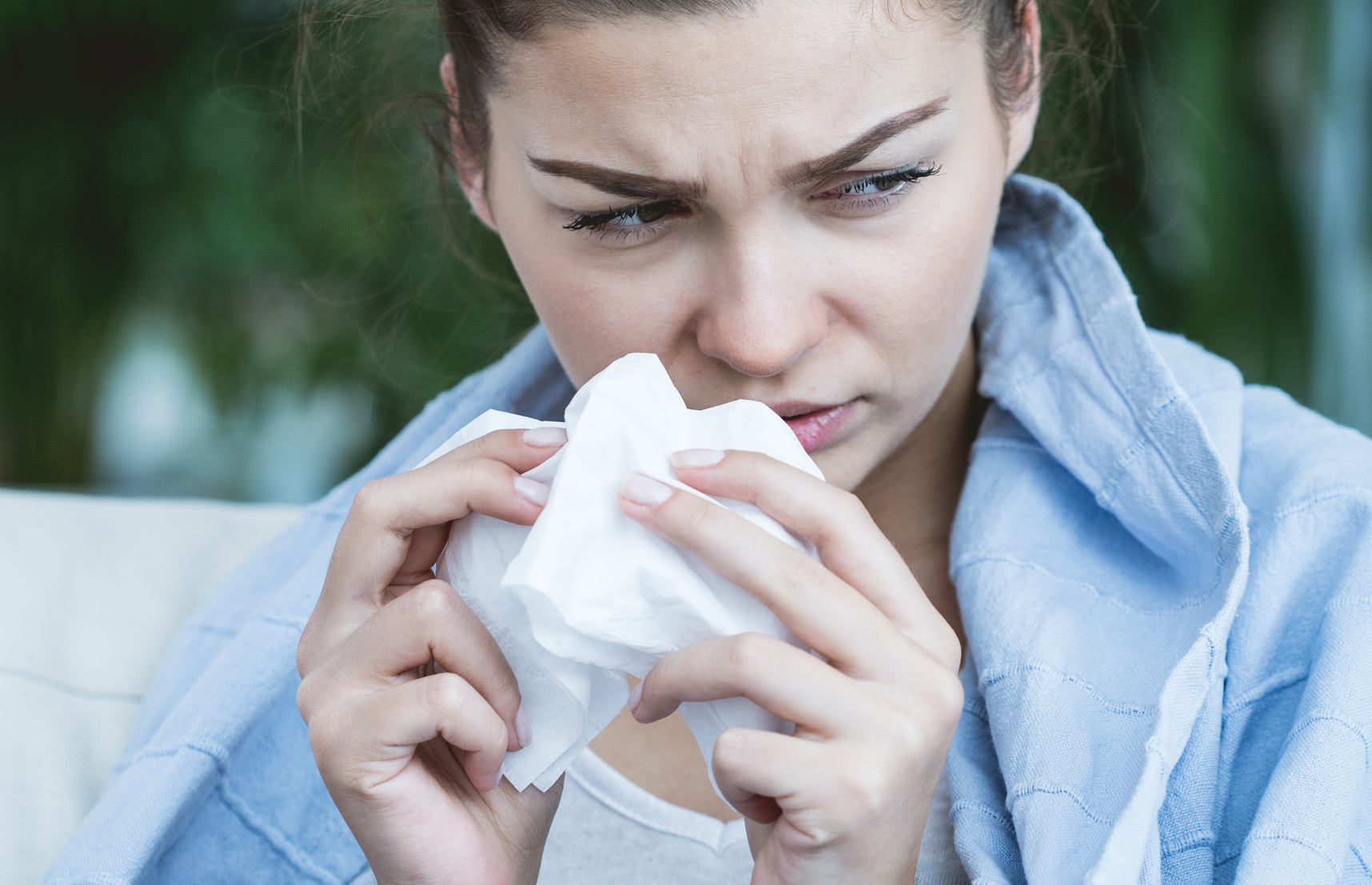 Image of ill woman with allergy blowing nose